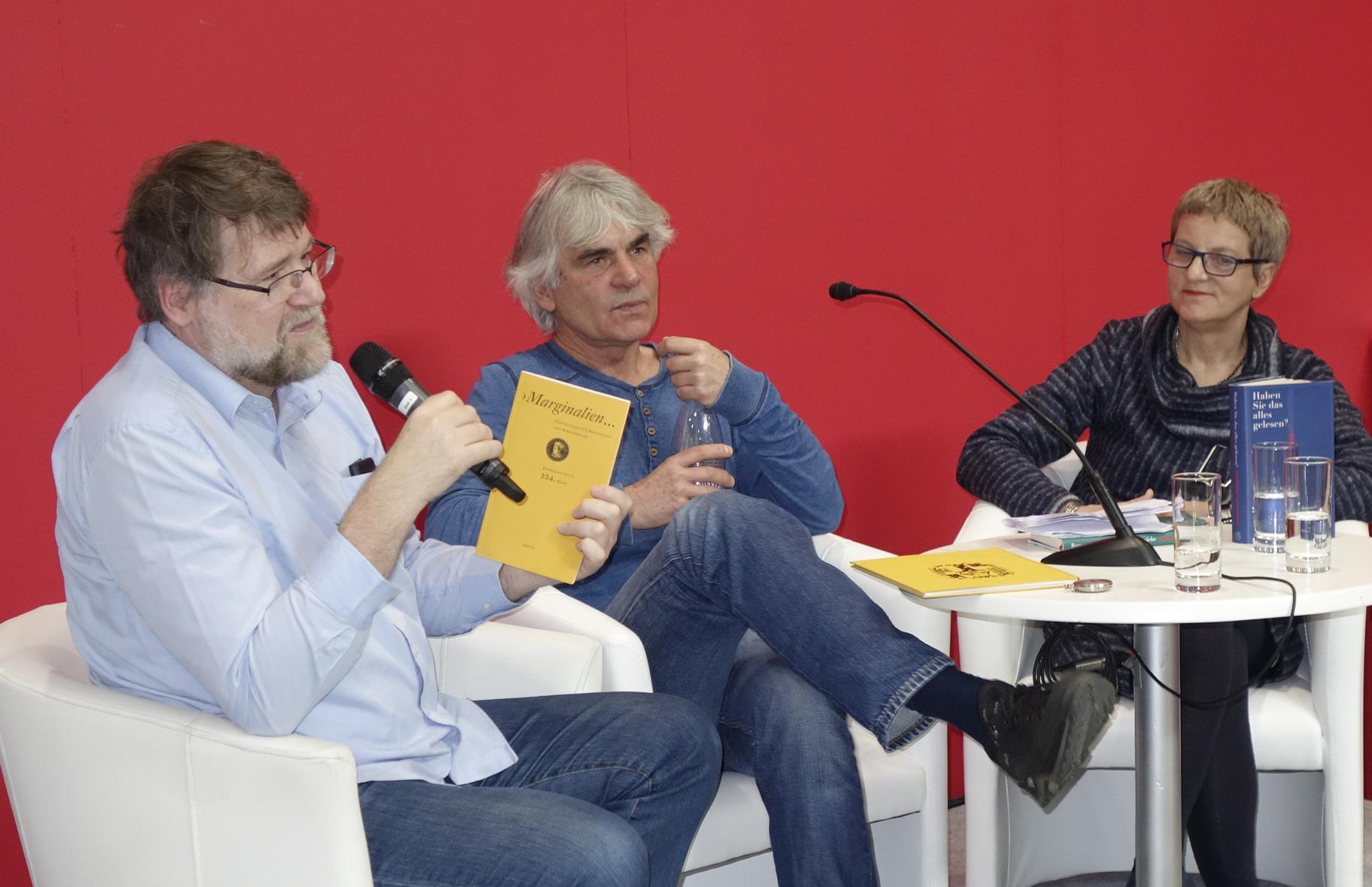 Moderator Jens-Fietje Dwars mit der aktuellen Ausgabe der »Marginalien«, in der Till Schröder das Künstlerbuch von Hartmut Andryczuk rezensiert hat.