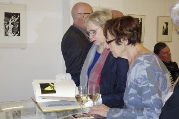 Zwei Besucherinnen blättern im Künstlerbuch »Paradies«.