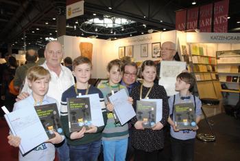 """Stolz zeigen die Bücherkinder ihr jüngstes Werk. Mit dabei sind Henry Günther (l.), der die Bücher gebunden hat, Pirckheimer-Vorsitzender Ralph Aepler und """"Büchervater"""" Armin Schubert.   © R. Wege"""