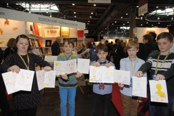Freudig halten die Bücherkinder ihre Porträtzeichnungen in Richtung Kamera. | © R. Wege