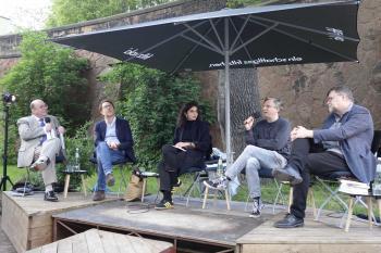 Personen auf einem Podium diskutieren